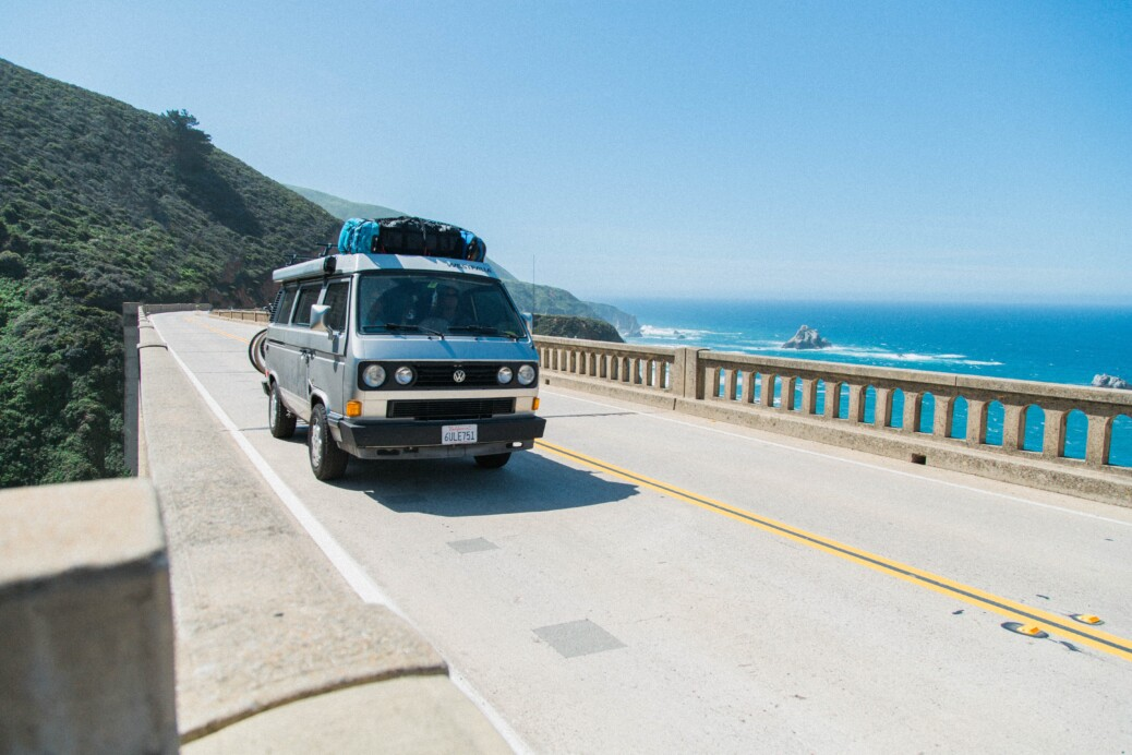 van driving along a bridge by the coast